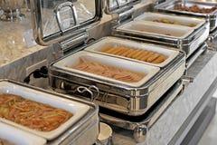 Cacerolas de vapor de la alimentación en la tabla de comida fría Imágenes de archivo libres de regalías