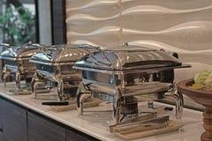 Cacerolas de vapor de la alimentación en la tabla de comida fría Fotos de archivo libres de regalías