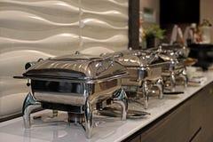 Cacerolas de vapor de la alimentación en la tabla de comida fría Fotografía de archivo