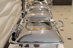 Cacerolas de vapor de la alimentación en la tabla de comida fría Fotos de archivo