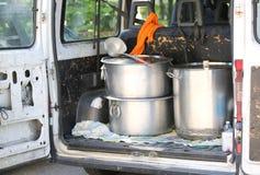cacerolas para transportar la comida en el tronco de la furgoneta en un campamento de refugiados Imagen de archivo libre de regalías