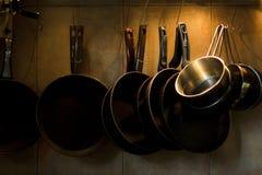 Cacerolas que cuelgan en la pared de la cocina Fotografía de archivo
