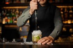 Cachaca de derramamento do barman no vidro de cocktail Processo de miliampère Fotografia de Stock