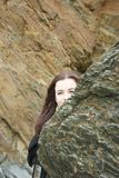 Cache-cache : la fille aux cheveux longs de brune se cache derrière une roche sur une plage photos stock