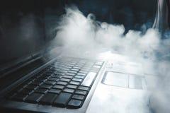 Cachimba que fuma mientras que trabaja en el ordenador port?til en casa, tema oscuro, cierre para arriba, l?neas de luz del sol fotos de archivo