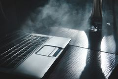 Cachimba que fuma mientras que trabaja en el ordenador port?til en casa, tema oscuro, cierre para arriba, l?neas de luz del sol imagen de archivo libre de regalías