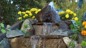 A cachoeira artificial no parque, água corre ao longo das etapas de pedra, movimento lento video estoque