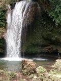 Cachoeira bonita sobre rochas naturais com folhas imagem de stock royalty free