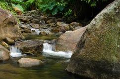 Cachoeira com a pedra do musgo verde na floresta tropical, Kiriwong Vil Imagens de Stock