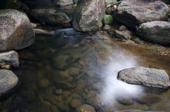 Cachoeira com a pedra do musgo verde na floresta tropical, Kiriwong Vil Foto de Stock