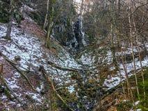 Cachoeira congelada com sincelos e um bocado de fluir a água em uma paisagem da floresta de Wasserfall Alemanha fotos de stock royalty free