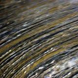 A cachoeira da cascata da água que flui a torrente espirra o fundo, grande close up horizontal detalhado, azul brilhante, dourado imagem de stock