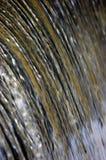 A cachoeira da cascata da água que flui a torrente espirra o fundo, grande close up vertical detalhado, azul brilhante, dourado,  Fotos de Stock Royalty Free