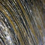 A cachoeira da cascata da água que flui a torrente espirra o fundo, grande close up vertical detalhado, azul brilhante, dourado,  Imagens de Stock