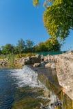 Cachoeira de conexão em cascata com os pedregulhos de pedra ao longo dos bancos, em um parque sob uma árvore Mezhygir ucrânia Foto de Stock