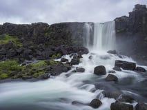 Cachoeira de Oxararfoss na reserva natural de Thingvellir Islândia com rochas vulcânicas e musgo, caindo da fissura em Ridg meio- Imagens de Stock Royalty Free
