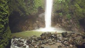 Cachoeira e lago bonitos da montanha na mulher da opinião aérea da floresta úmida na cachoeira tropical no córrego da floresta úm vídeos de arquivo