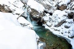 A cachoeira e o gelo azuis pequenos formaram em um córrego da montanha no inverno Fotos de Stock Royalty Free