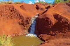 Cachoeira e rio que encontram sua maneira através das rochas vermelhas, garganta de Waimea, Kauai, Havaí foto de stock royalty free