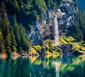 Cachoeira efervescente no lago Oeschinensee Manhã esplêndida do verão nos cumes suíços, lugar da vila de Kandersteg, Suíça, imagem de stock