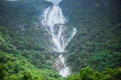A cachoeira enorme Dudhsagar e a ponte de estrada de ferro que passa através dela imagens de stock