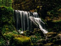 Cachoeira enorme nas ruínas de um moinho velho na floresta imagens de stock royalty free