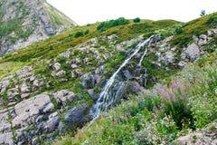 Cachoeira entre as montanhas nos cumes imagem de stock royalty free