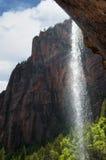 Cachoeira entre montanhas vermelhas e árvores verdes Foto de Stock