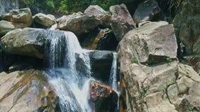 Cachoeira espumosa fantástica próxima da vista aérea em grandes rochas filme