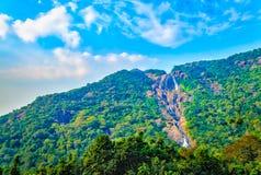 Cachoeira estreita que divide uma montanha verde Imagem de Stock