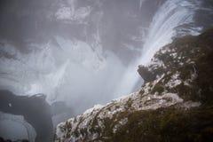 Cachoeira islandêsa na neve e na chuva do inverno Imagem de Stock