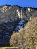 Cachoeira lindo no vale famoso de Lauterbrunnen e cumes suíços com reflexão da luz solar na estação do inverno foto de stock
