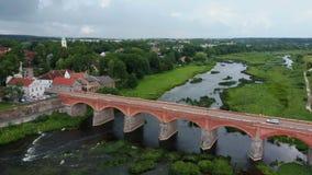 A cachoeira a mais larga em Europa em Letónia Kuldiga e na ponte do tijolo através do dron regional do venta do rio disparou vídeos de arquivo