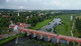 A cachoeira a mais larga em Europa em Letónia Kuldiga e na ponte do tijolo através do dron regional do venta do rio disparou filme