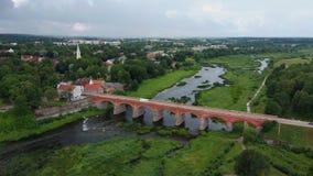 A cachoeira a mais larga em Europa em Letónia Kuldiga e na ponte do tijolo através do tiro regional de Venta Dron do rio video estoque