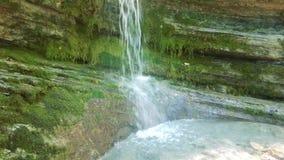 Cachoeira no volume de água puro da floresta entre rochas velhas filme