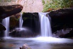 Cachoeira pequena com Moss Covered River Stones na luz brilhante de Sun nas montanhas fumarentos imagem de stock royalty free