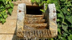 Cachoeira pequena da água em pedras artificiais no parque, água corrente constante, gotejando para baixo, em um movimento lento filme