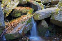 Cachoeira pequena entre bloulders Imagens de Stock