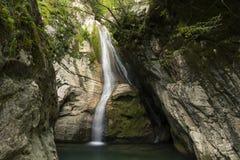 Cachoeira pequena que cai em uma lagoa imagens de stock royalty free