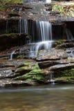 Cachoeira pequena sobre as rochas molhadas cobertas no musgo e nas folhas de outono que fluem em um córrego abaixo imagens de stock