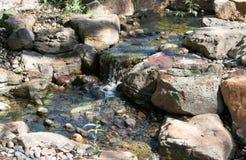 Cachoeira que cai lentamente contra rochas Fotografia de Stock Royalty Free