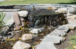 Cachoeira que cai lentamente contra rochas Imagens de Stock