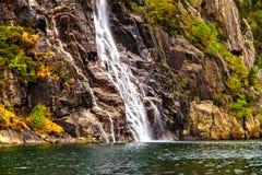 Cachoeira que flui abaixo do penhasco um córrego estreito Imagens de Stock Royalty Free