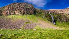 Cachoeira que flui das montanhas, Islândia Imagens de Stock
