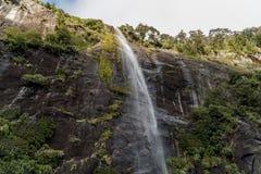 Cachoeira que flui sobre um penhasco em Milford Sound, Nova Zelândia imagens de stock
