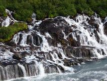 Cachoeiras de Hraunfossar que parecem sair do solo da lava fotos de stock