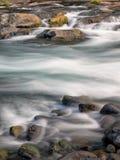 Cachoeiras e logs musgosos e rochas Imagens de Stock
