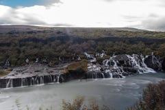 Cachoeiras majestosas com rochas e grama ao redor Fotos de Stock Royalty Free