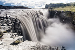 Cachoeiras majestosas com rochas e grama ao redor Imagem de Stock